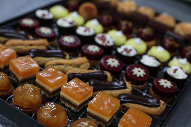 Dessert tray featuring mini tartlets, chocolate eclairs and cream puffs.